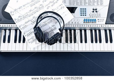 Headphones with music notes on synthesizer poster