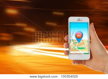 Hand holding mobile smart phone with interface taxi on night background