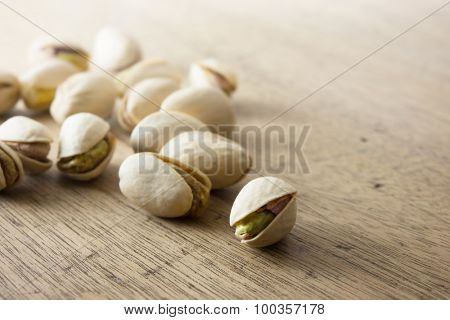 Pistachio nuts with shell on a old kitchen table.