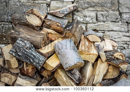 Chopped Wood Besides Stone Wall