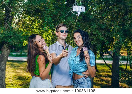 Group of friends taking picture themselves with monopod use smart phone take photograph selfie stick