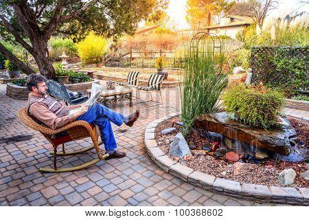 Man is reading a newspaper on a patio in a cozy garden