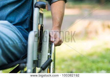 Detail of a man using a wheelchair in a park. Copy-space on the right side poster
