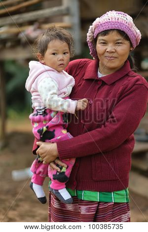 MAE KLANG LUANG, THAILAND, DECEMBER 31, 2014 : A Karen tribe woman in traditional clothes is holding her kid in the village of Mae Klang Luang in the Doi Inthanon national park, Thailand