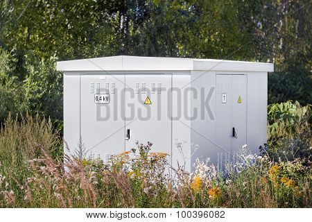 Electric Power Transformer In A Meadow