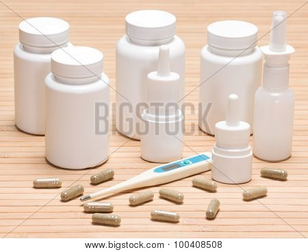 Set of various cold and flu remedies. Jars of medicines scattered capsules electronic thermometer nasal sprays poster