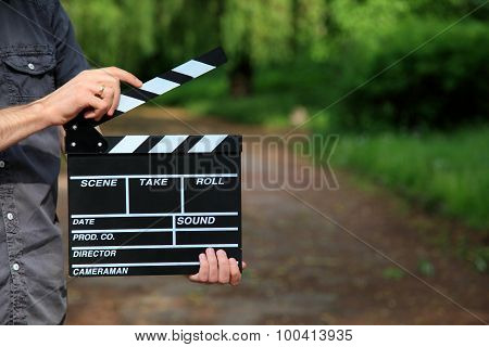 clapperboard in man hand, close up background