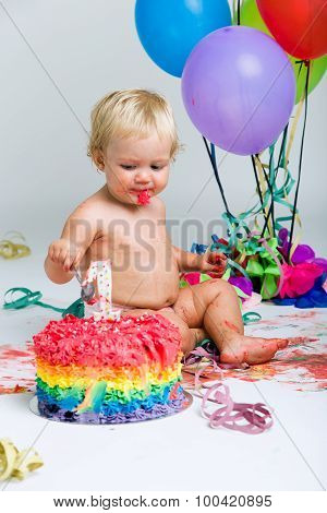Baby Girl Celebrating Her First Bithday With Gourmet Cake And Balloons.