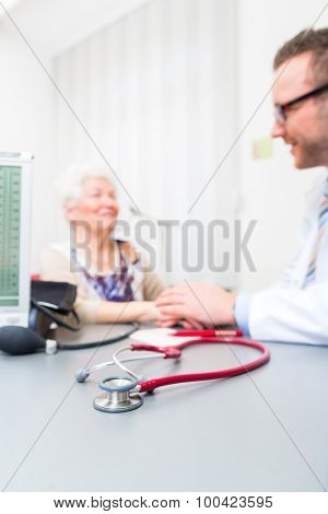 Doctor sitting with pensioner in surgery consultation hour at desk poster