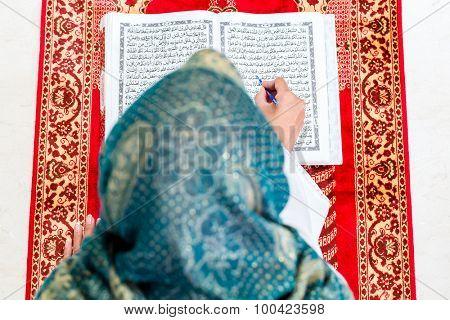 Asian Muslim woman reading Koran or Quran on praying carpet wearing traditional dress