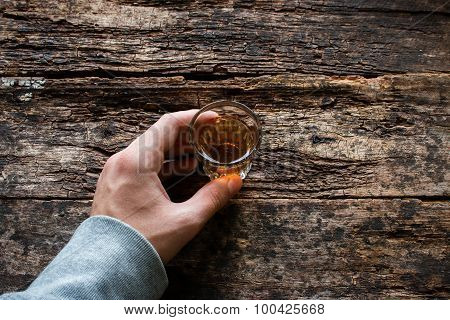 Man Holding A Glass Of Alcohol On A Wooden Background