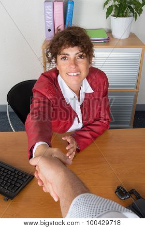 Woman At Work  Happy And Looking At The Camera Handshaking