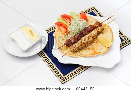 Souvlaki or kebab, grilled meat on pita bread with tomatoes and cucumbers, white plate.