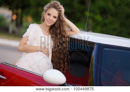 Pregnant brunette girl near her car