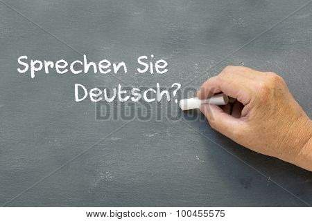 Hand on a chalkboard with the German words Sprechen Sie deutsch (Do you speak German). Learning German language class concept showing teacher hand writing on the blackboard. poster