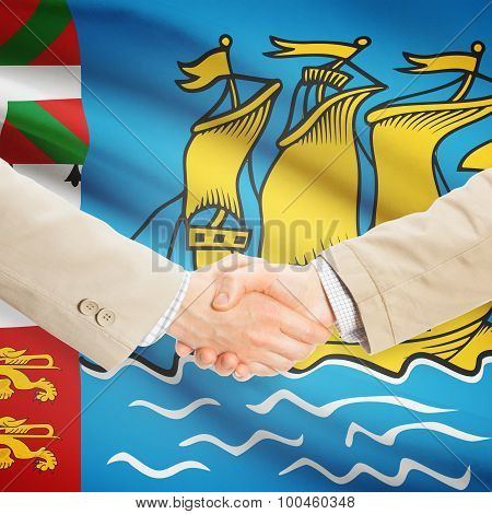 Businessmen shaking hands with flag on background - Saint-Pierre and Miquelon poster