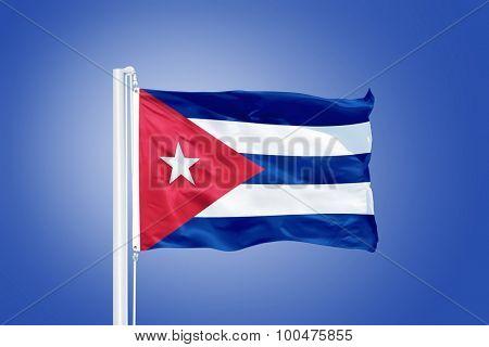 Flag of Cuba flying against a blue sky.