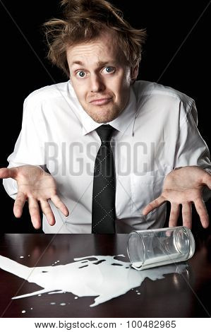 Businessman shrugs and helpless after knocking over glass of milk on table, desaturated with black background