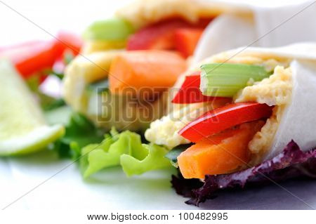Close up on mini tortilla wraps with raw vegetable sticks