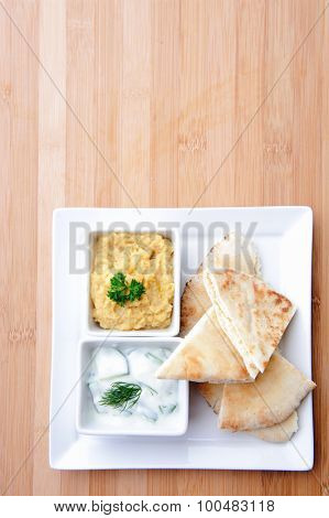 Variety of dips with flatbread; Tzatziki and humus/hummus