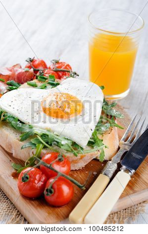 Big breakfast with egg, tomato, bacon and rocket on toast served on rustic wooden board with oj orange juice . heart conscious