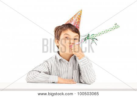 Little kid with party hat sitting at a table and blowing a favor horn isolated on white background