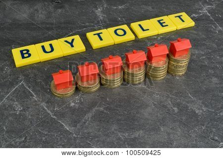 A rising stack of coins with toy houses on top and the words; ''Buy To Let'' in the background. poster