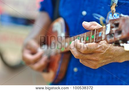 music man is playing steel string indian lute in festival thailand before raining season the body of this little guitar made from wood
