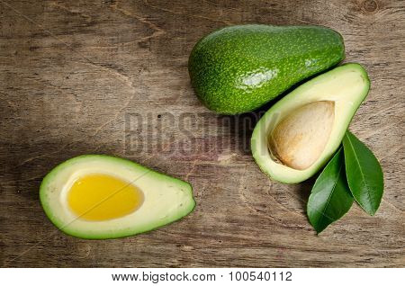 Fresh Fruits Avocado And  Avocado Like A Bowl For Oil On Wooden Background