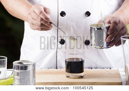 Chef putting condensed milk in to Hot coffee poster