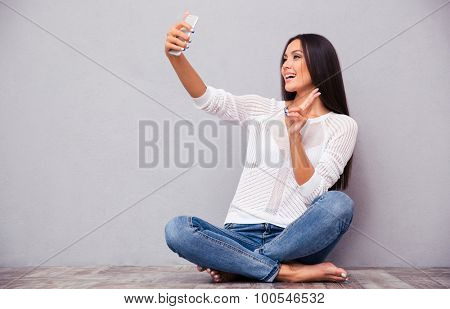 Portrait of a happy woman sitting on the floor and making selfie photo on smartphone on gray background