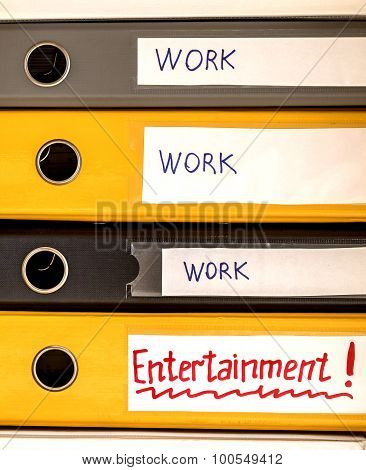 Work and life balance Conceptual image describing the correct business and private life balance. Three office folders in row with word WORK and ENTERNAINMENT written on latter poster