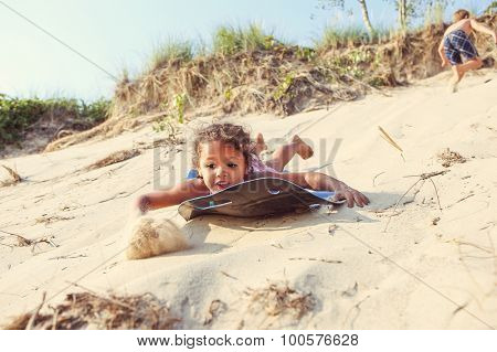 Young girl sliding down a sand dune on a sled in the summer. Some motion blur on girl and sand.