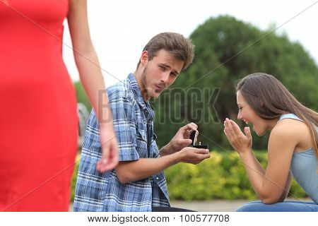 Cheater man cheating during a marriage proposal with his innocent girlfriend poster