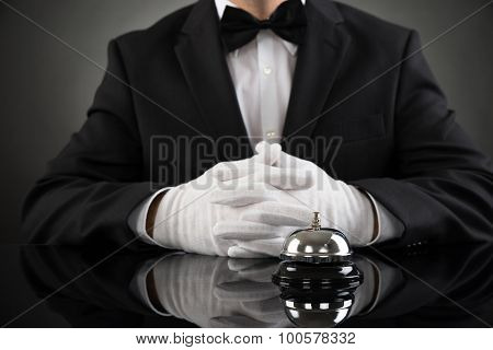 Waiter With Service Bell At Desk