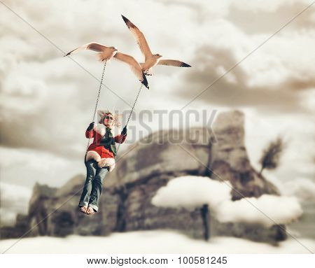 a pretty girl being carried on a swing by two seagulls in a surreal digital manipulation with a cliff and clouds in the background (FOCUS IS ON THE BIRD)