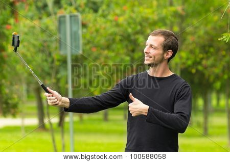 Hispanic man posing with selfie stick in park environment smiling