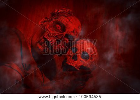 Frightening bloody zombie man with a skull in blood-red light. Halloween.