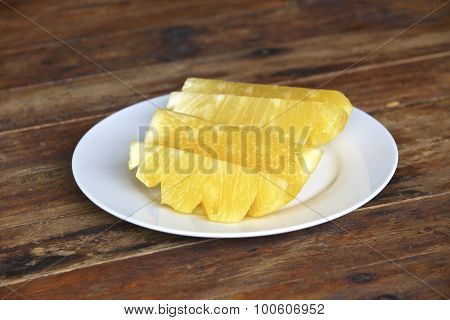 Pineapple pieces placed in white plate on old wooden floor.