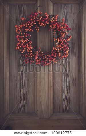 Fall berry wreath hanging on a wooden door