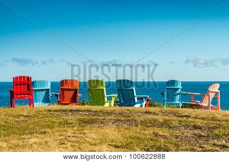 7 empty colourful chairs facing the sea