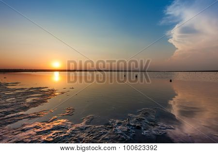 sunset over water surface of salted sea bay