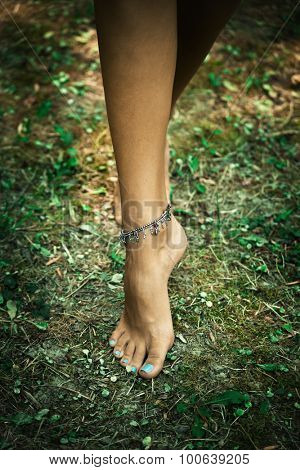woman foot with ankle bracelets on ground with grass in forest, shot from above, selective focus, natural light