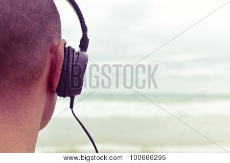 closeup of a young man listening to music with headphones in front of the sea, with a filter effect