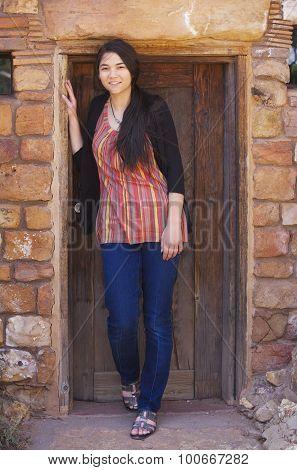Biracial Teen Girl Standing In Brick Doorway Of Home