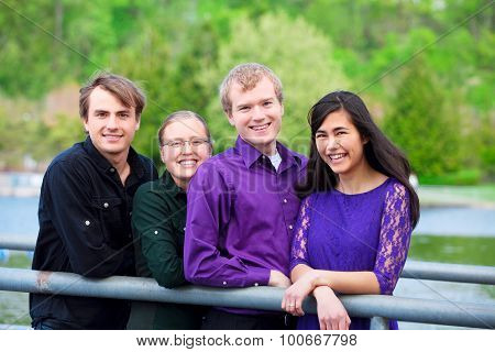 Four Young Multiethnic Friends Together Outdoors By Lake