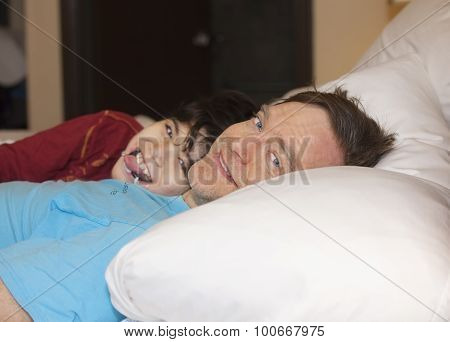 Father Sleeping In Bed With Disabled Young Son, Laughing And Smiling