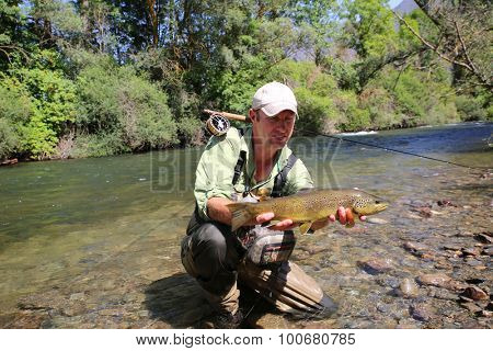 Fly-fisherman holding brown trout recently caught poster