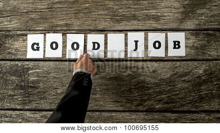 Business leader assembling phrase GOOD JOB with white cards with letters on them on wooden background in order to compliment and encourage his team of employees for further successful endeavours. poster