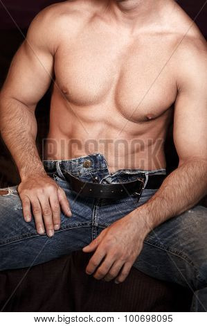 Sexy macho man body sitting on bed open jeans poster